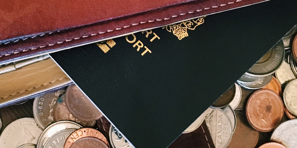 Photo of a passport and coins. Published under CC0 Public Domain. https://unsplash.com/photos/5wTR91A3mio